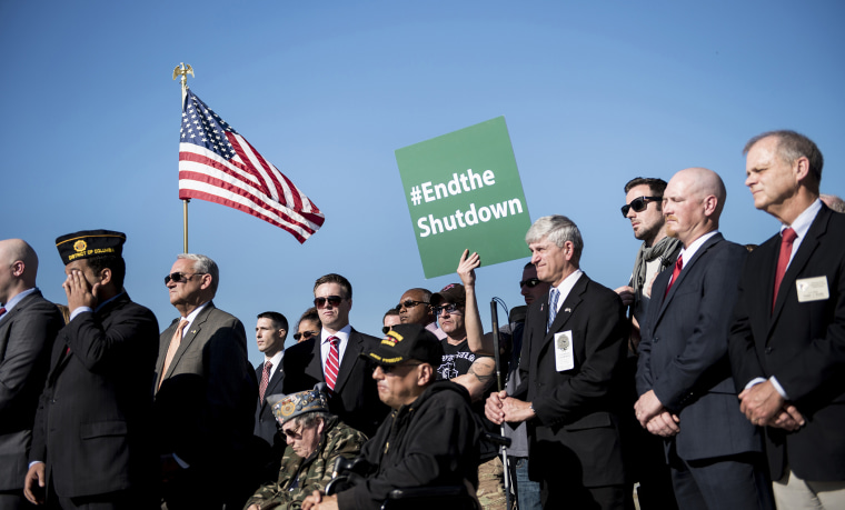 Activists listen to speakers during a rally at the World War II Memorial