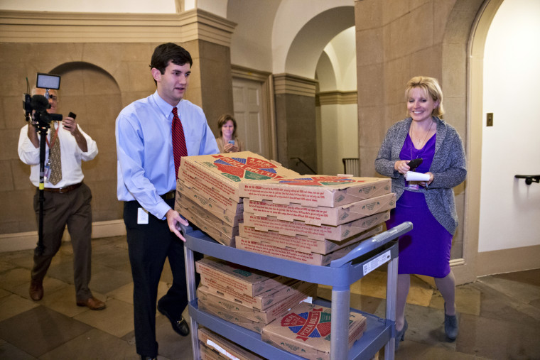 An aide brings a cart stacked with pizza to the office of Speaker of the House John Boehner, as movement toward ending the government shutdown was suddenly halted, at the Capitol in Washington, Tuesday night, Oct. 15, 2013.