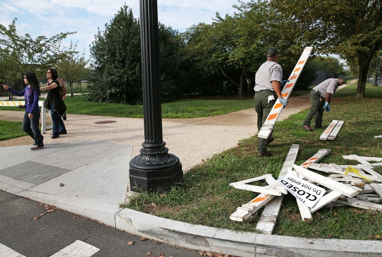Tourists walk past as U.S. Park Service workers remove barricades on October 17, 2013 in Washington, DC.