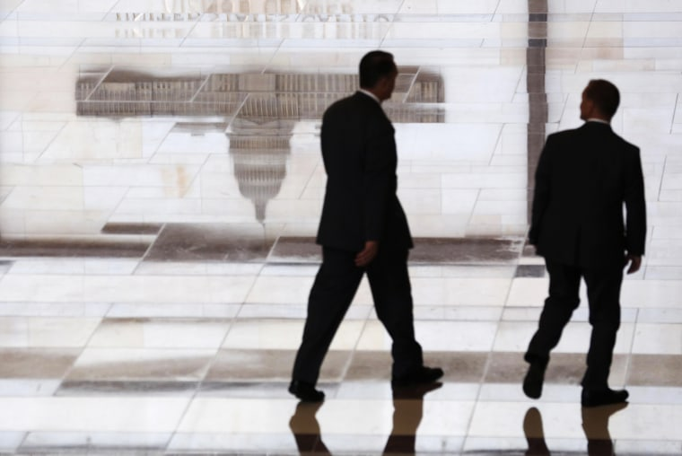 Men walk past a reflected image of the Capitol inside the U.S. Capitol Visitors Center in Washington  October 16, 2013.