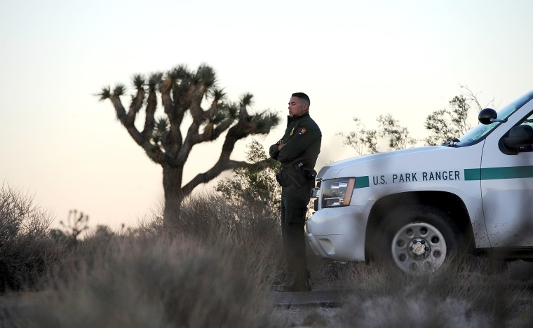 Park Ranger Dylan Moe stands guard as the sun sets at the entrance to Joshua Tree National Park