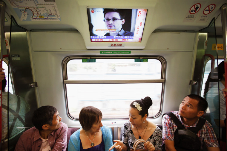 Passengers watch a television screen broadcasting news on Edward Snowden on a train in Hong Kong June 14, 2013.