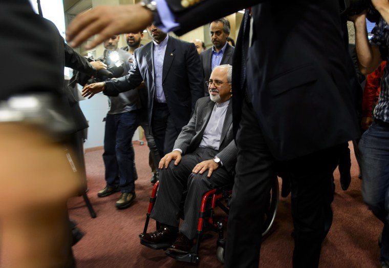 Iranian Foreign Minister Mohammad Javad Zarif leaves with a weelchair a press conference closing a two-day of closed-door nuclear talks on October 16, 2013 in Geneva.