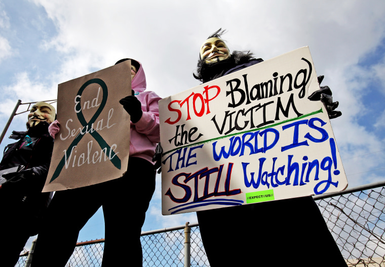 Protesters hold signs outside of the Jefferson County Justice Center and Jail in Steubenville, Ohio, on Wednesday, March 13, 2013.