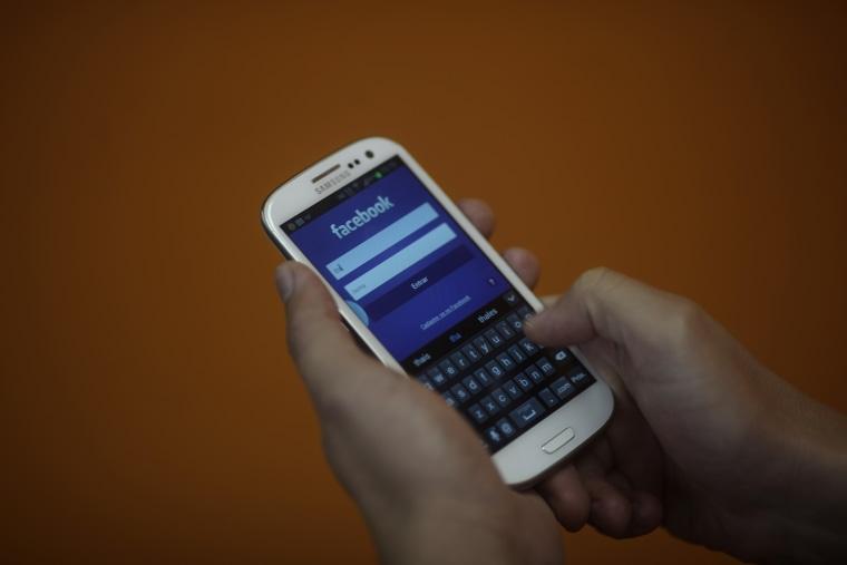A smartphone user logs into his Facebook account in Rio de Janeiro on April 15, 2013.