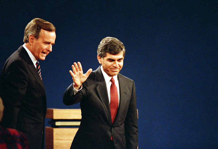 Democratic presidential candidate Michael Dukakis acknowledges the auditorium as Republican presidential candidate,Vice President George Bush, looks on after their final debate in Los Angeles, California, Oct, 13, 1988.