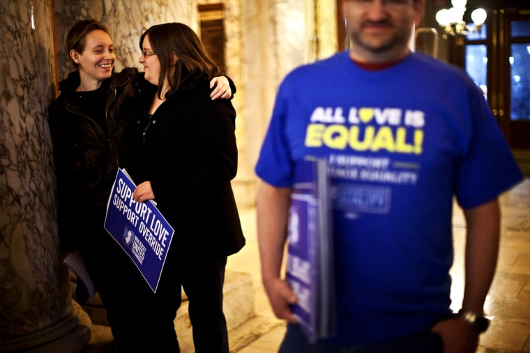 Lauren and Katelynn hug each other as they attend the first massive gay wedding ceremonies at City Hall in the early morning hours of October 21, 2013 in Newark, New Jersey.