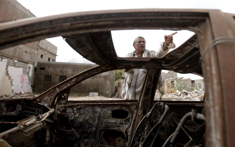 Muhammad Saleh Abdullah, 65, a resident of the southern Yemeni town of Jaar, gestures as he stands near his car destroyed by an air strike last year that was targeting al Qaeda-linked militants, in Jaar February 1, 2013