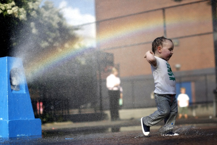 A young boy cools off in the water from a playground sprinkler in the Brooklyn borough of New York