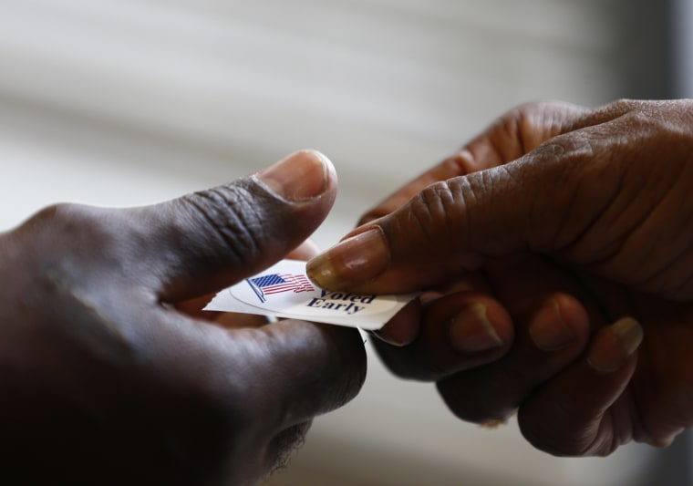 A poll worker hands a sticker to a voter at a polling place in Charlotte, NY.