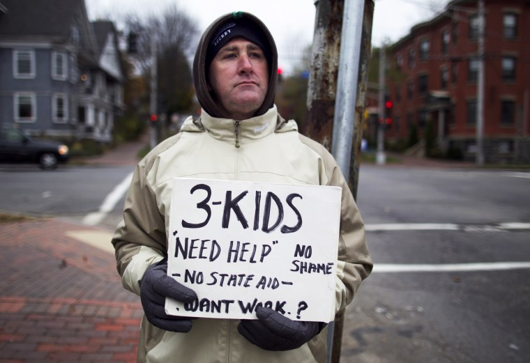 Brian Adams, 42, stands on the corner of State Street and Park Avenue, in Portland, Maine, Wednesday, Nov. 7, 2012. Adams, who lives with his fiance and their three children on Munjoy Hill, lost his job as a mason.