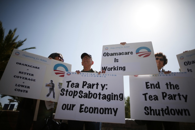 Demonstrators hold up signs at an education and awareness event on the Affordable Care Act and protest against Tea Party officials they say are threatening an economic shutdown, in Santa Monica, Calif. on Oct. 10, 2013.
