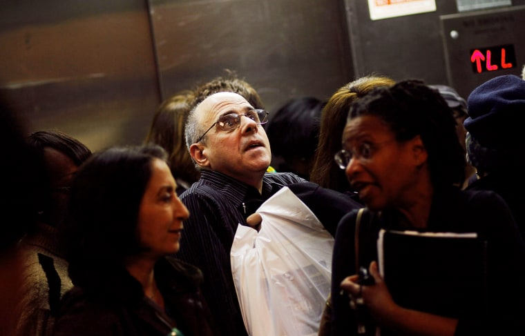"""Older job-seekers crowd into an elevator on the way to a employment seminar at a \""""Work Search\"""" event aimed at older unemployed people in New York City."""