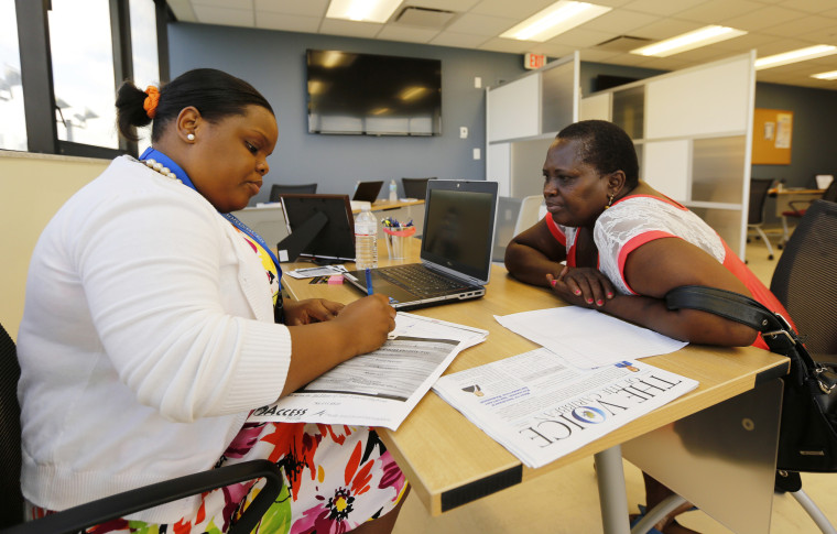 Certified Application Counselor Sheslie Caze (L) takes information from a woman as she inquired about the Affordable Care Act insurance at the Borinquen Medical Center in Miami on Oct. 1, 2013.