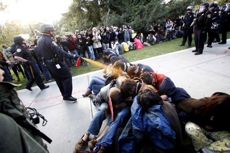 In this Nov. 18, 2011 file photo, University of California, Davis Police Lt. John Pike uses pepper spray to move Occupy UC Davis protesters while blocking their exit from the school's quad in Davis, Calif.