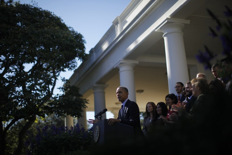 President Barack Obama stands with supporters of his health care law during an event in the Rose Garden of the White House