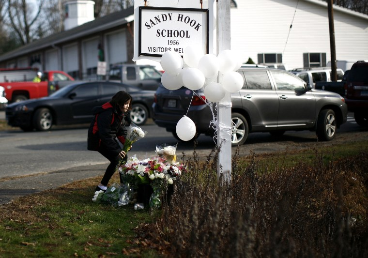 A girl places flowers at a memorial at a sign for Sandy Hook Elementary School in Sandy Hook, Conn.