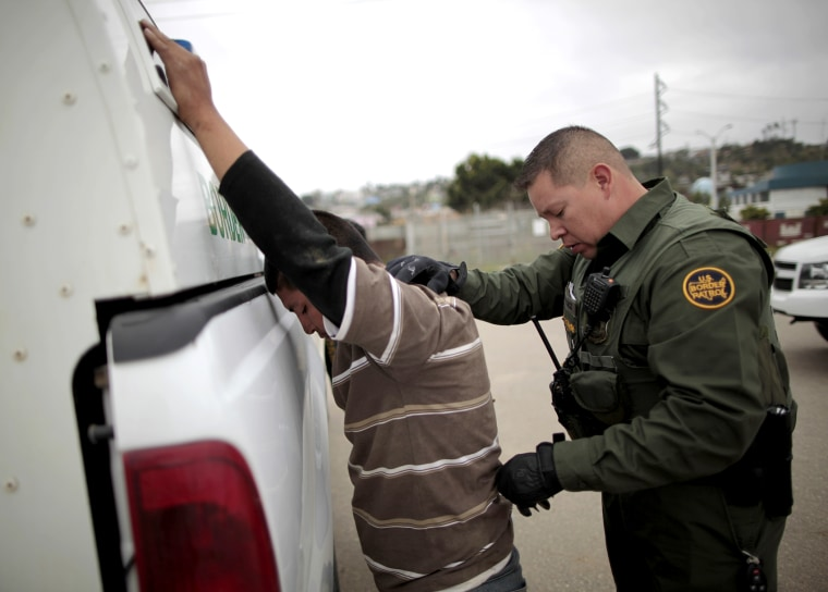 A United States border patrol agent catches an undocumented immigrant crossing from Mexico to the U.S. in San Ysidro