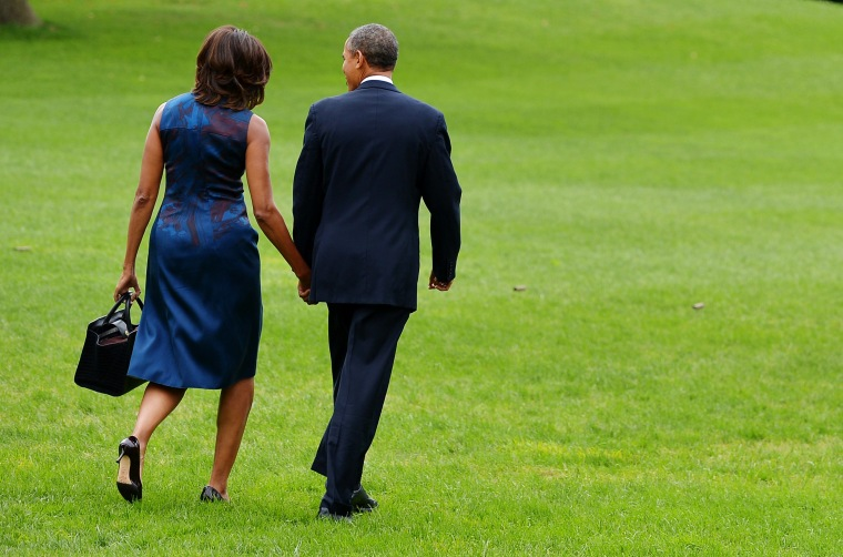 US President Barack Obama and First Lady Michelle Obama make their way to board Marine One on the South Lawn of the White House on September 23, 2013 in Washington, DC.