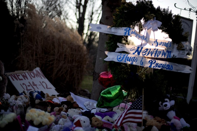 The sun sets behind a memorial for the Sandy Hook Elementary School shooting victims, Wednesday, Dec. 19, 2012, in Newtown, Conn.