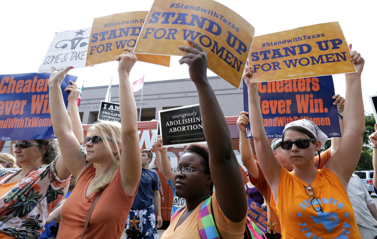 In this July 9, 2013 file photo, opponents and supporters of an abortion bill hold signs near a news conference outside the Texas Capitol, in Austin, Texas.