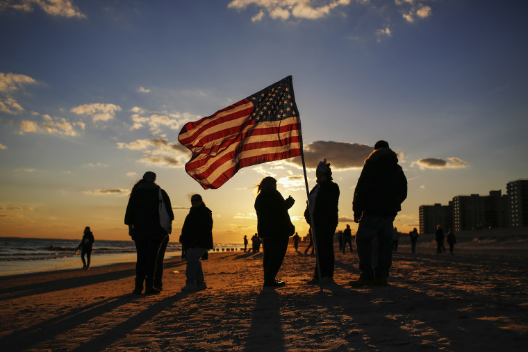 People stand with an American flag during a remembrance ceremony along the beachfront damaged by hurricane Sandy in October 2012 in the borough of Queens in New York