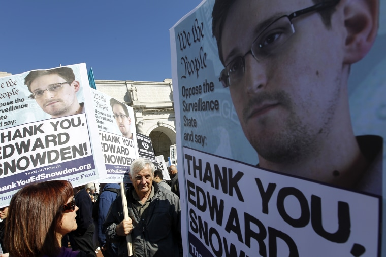 Demonstrators holds up banners with the photo of Edward Snowden during a protest outside of the U.S. Capitol in Washington, on Saturday, Oct. 26, 2013.
