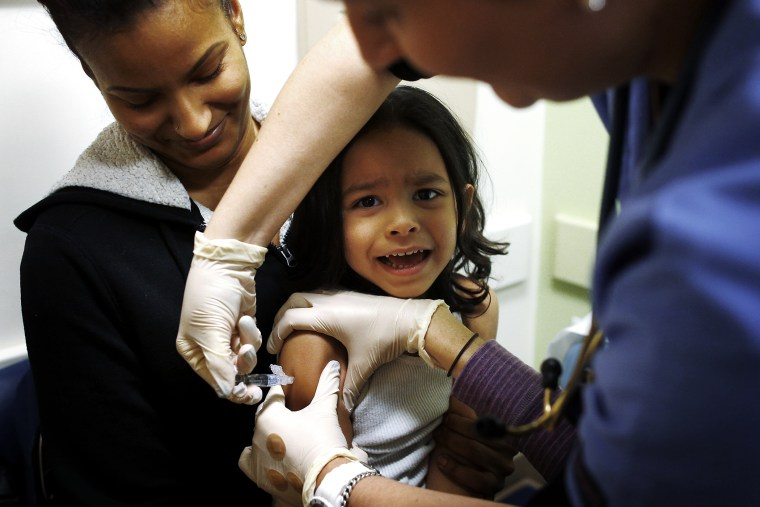 Mercado sits in his mother's lap while getting an influenza vaccine at Boston Children's Hospital in Boston