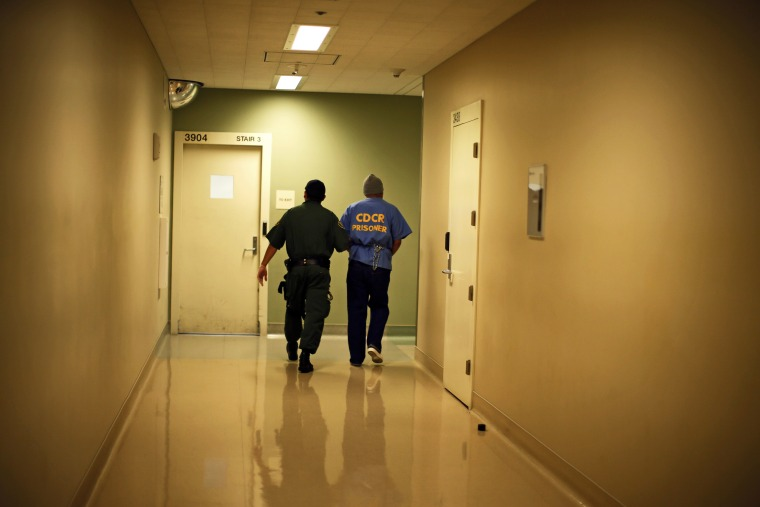 Albert Ruiz, 50, who is on death row for murder, is led down a corridor at San Quentin state prison in San Quentin, California June 8, 2012.