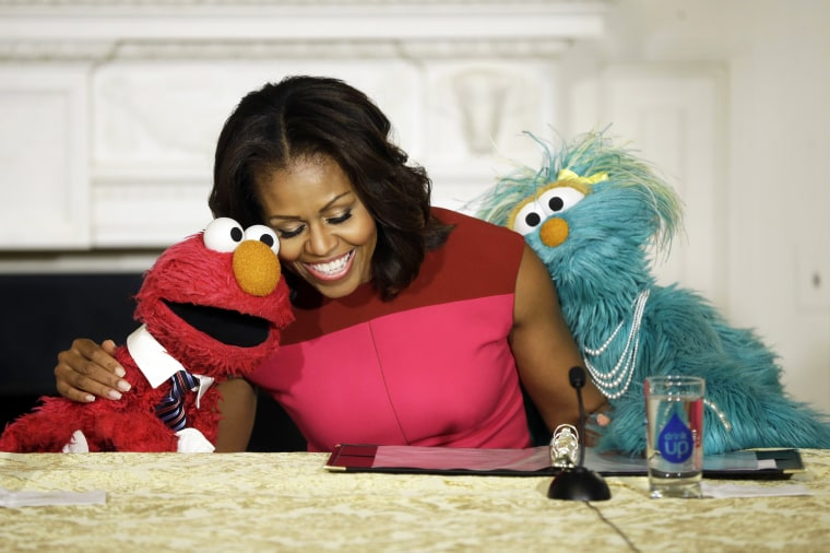 First lady Michelle Obama with Sesame Street characters Elmo and Rosita, as they help promote fresh fruit and vegetable consumption to kids at the White House, Wednesday, Oct. 30, 2013.