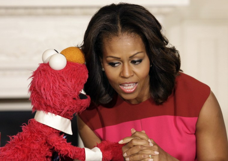 U.S. first lady Michelle Obama listens to Sesame Street character Elmo after delivering remarks on marketing healthier foods to children at the White House, October 30, 2013.