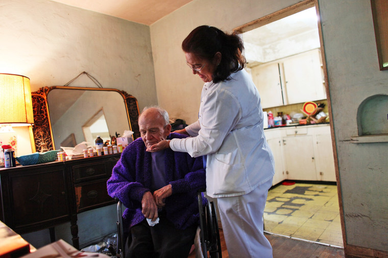 United HomeCare Services home health aide Wendy Cerrato visits with Robert Granville as she washes and feeds him in Miami, Florida.