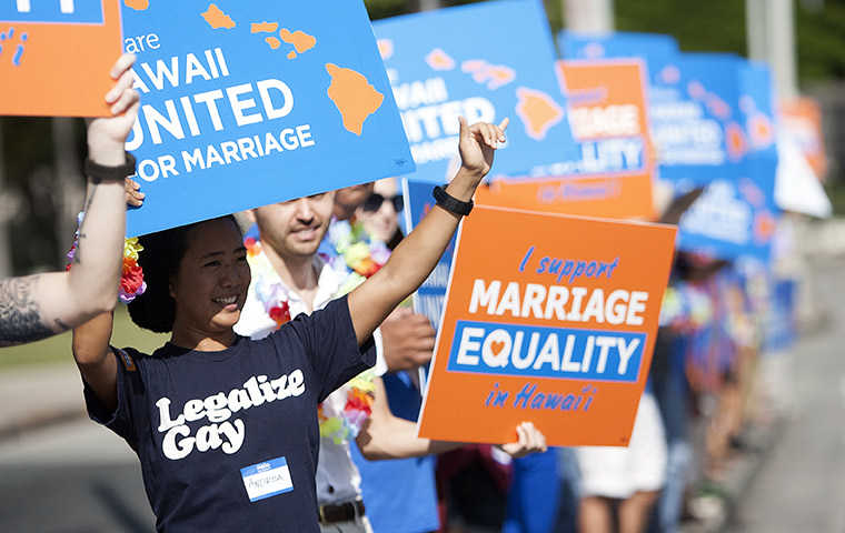 Keri Bias (L) holds a sign in support of same sex marriage in front of the Hawaii State Capital in Honolulu October 28, 2013.