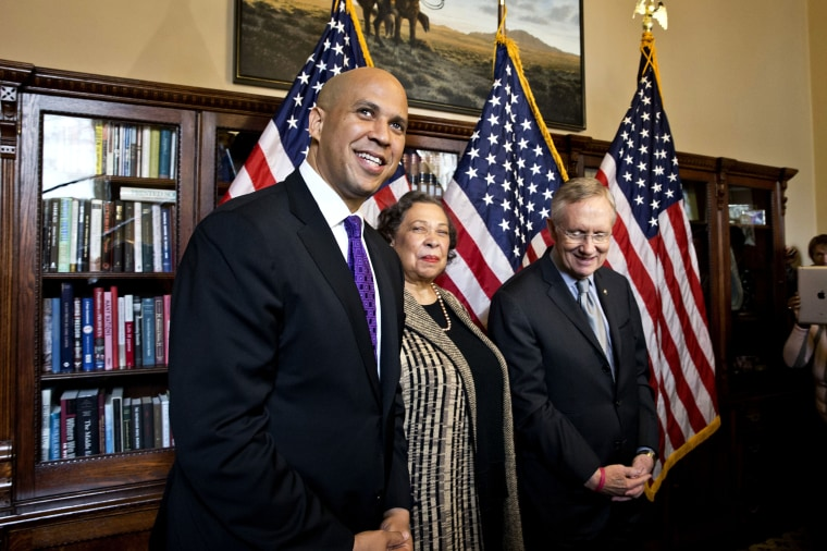 Newly-elected Democratic senator from New Jersey, former Newark Mayor Cory Booker, left, and his mother, Carolyn Booker, meet with Senate Majority Leader Harry Reid of Nev., before being officially sworn in on the floor of the Senate, Thursday, Oct. 31, 2