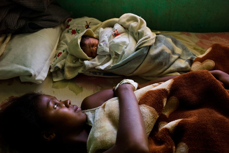 Anik, a sixteen-year-old mother, lies next to her newborn child inside the General Government Hospital in Tulear, Madagascar in November 2012.