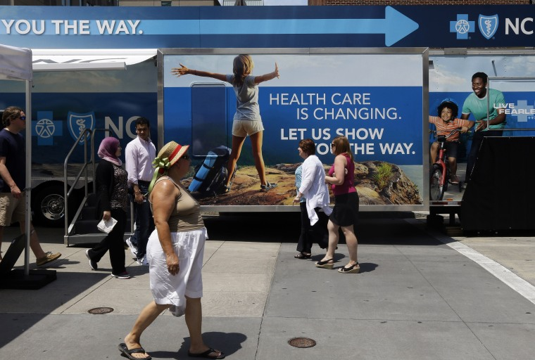 Pedestrians pass by a Blue Cross Blue Shield of North Carolina trailer at the downtown farmer's market in Raleigh, N.C., July 17, 2013.