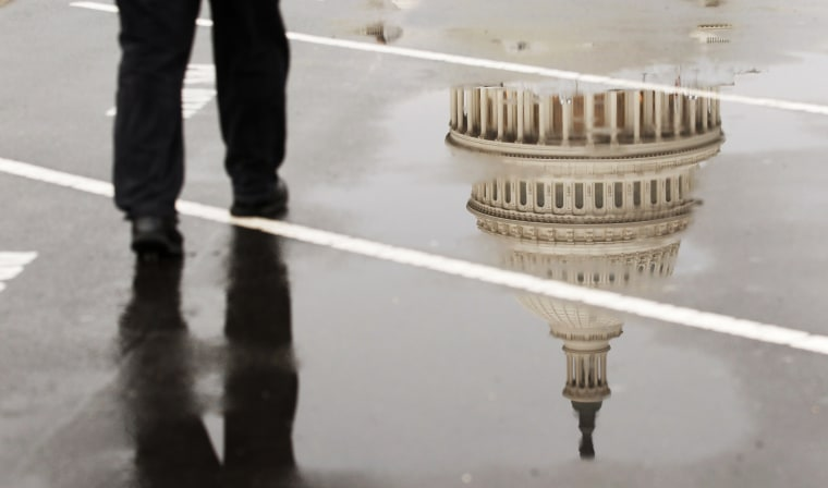 The dome of the U.S. Capitol Building is reflected in a puddle on a rainy morning in Washington.