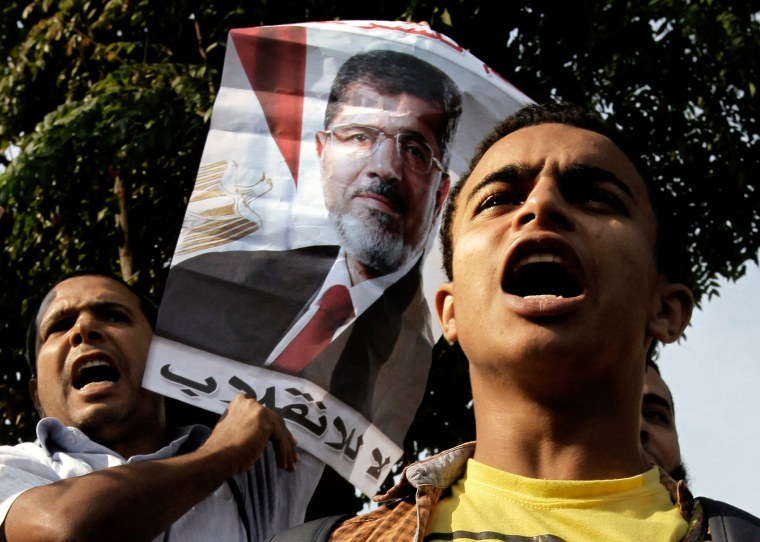 """Supporters of Egypt's ousted President Mohammed Morsi raise his poster with Arabic that reads, """"no to the coup"""", during a protest in front of the supreme constitutional court in Cairo, Egypt, Monday, Nov. 4, 2013."""