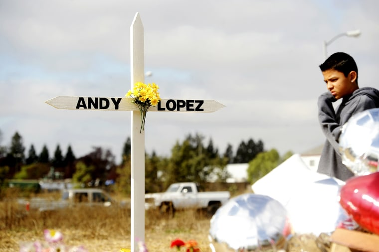 A boy passes a memorial marking the location where sheriff's deputies shot and killed 13-year-old Andy Lopez Cruz in Santa Rosa, Ca., October 27, 2013.