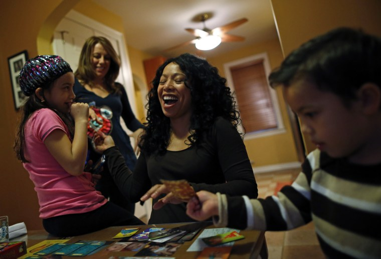 Mercedes Santos shares a laugh with her partner, Theresa Volpe, while playing cards with their kids at home in Chicago, Illinois, December 22, 2012.