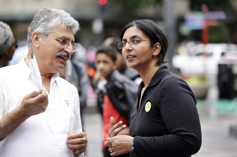 Seattle City Council candidate Kshama Sawant, right, speaks with a restaurant worker during a demonstration in Seattle, Aug. 1, 2013.