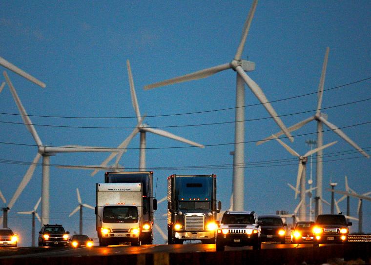 Diesel trucks and cars pass windmills along the 10 freeway near Banning, California.