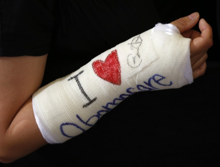 Cathey Park of Cambridge, Massachusetts shows her cast signed by U.S. President Barack Obama after he spoke about health insurance at Faneuil Hall in Boston, October 30, 2013.