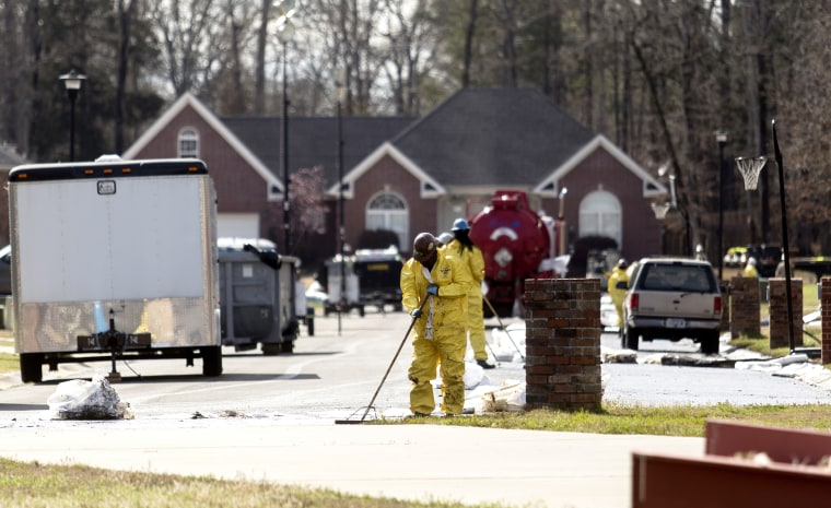 Emergency crews work to clean up an oil spill in front of evacuated homes on Starlite Road in Mayflower
