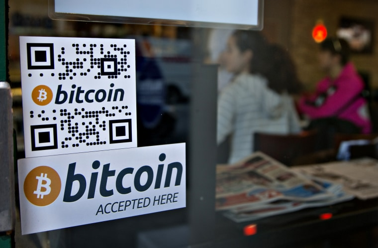 Signs on window advertise a bitcoin ATM machine that has been installed in a Waves Coffee House in Vancouver, British Columbia October 28, 2013.