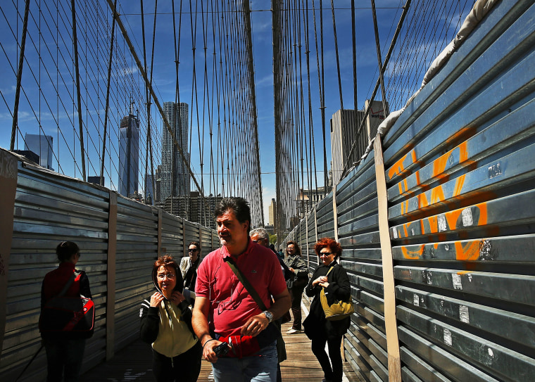 People walk past protective metal sheeting along the Brooklyn Bridge on April 30, 2013 in New York City.