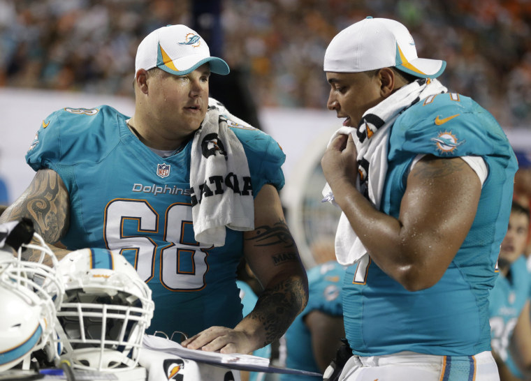 Miami Dolphins guard Richie Incognito (68) and tackle Jonathan Martin (71) looks over plays during the second half of an NFL preseason football game against the Tampa Bay Buccaneers, Saturday, Aug. 24, 2013 in Miami Gardens, Fla.