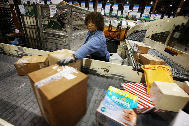 Bobbi Crump moves mail on a conveyor, December 17, 2012 in Elk Grove Village, Illinois.
