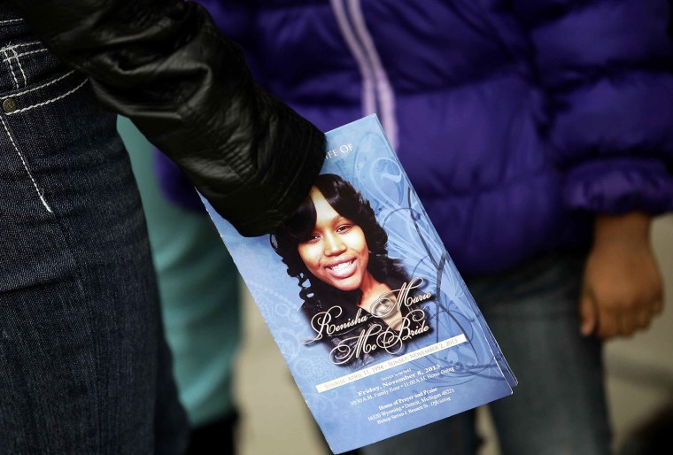 A mourner holds an obituary displaying a picture of shooting victim Renisha McBride during her funeral service in Detroit, Michigan November 8, 2013.