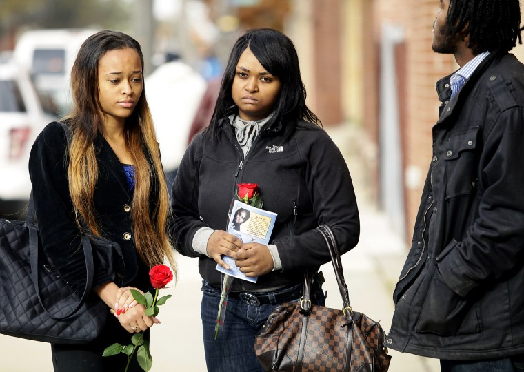 Mourners hold roses after the funeral service for 19-year-old shooting victim Renisha McBride in Detroit, Michigan, November 8, 2013.